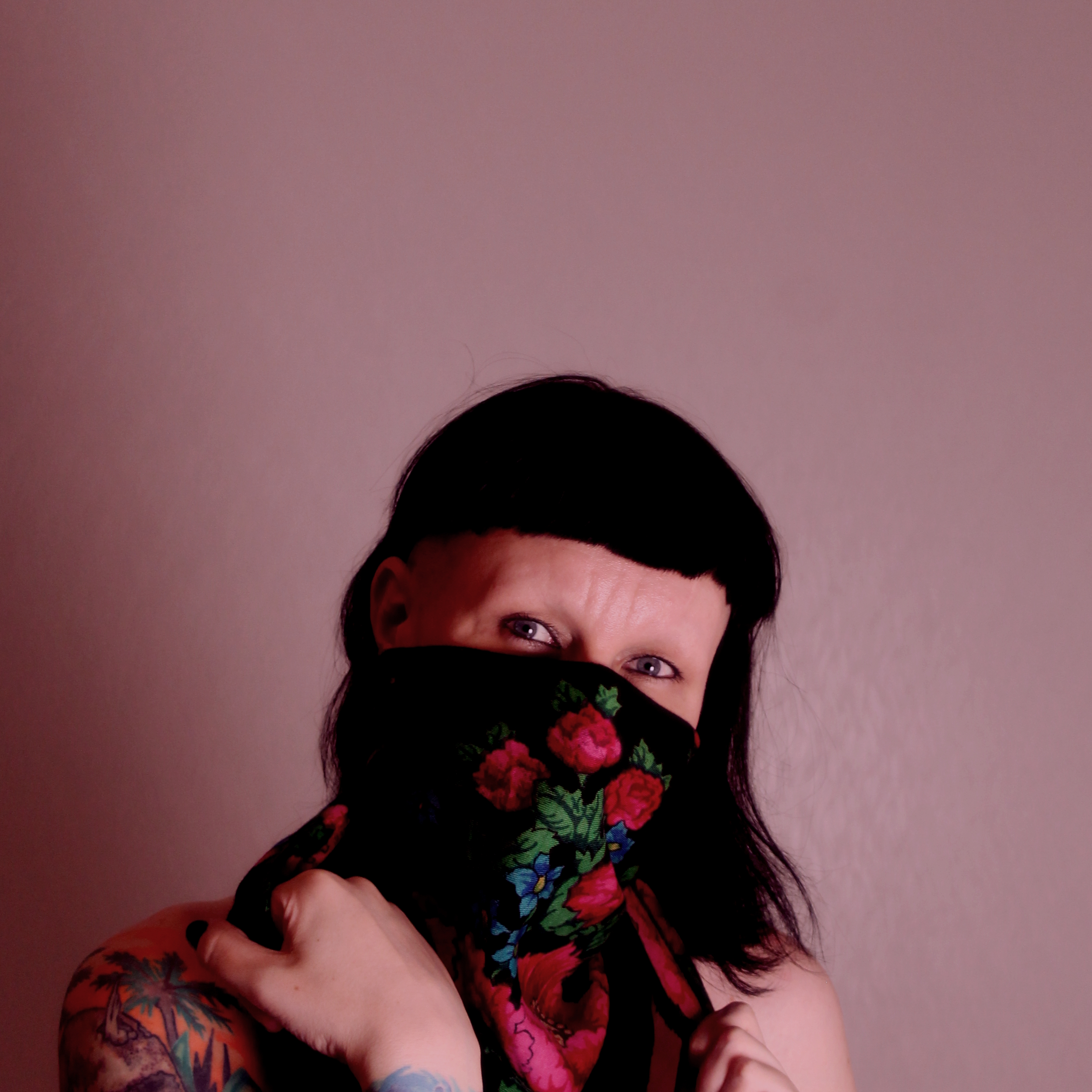 image of Pihla Lehtinen in front of a pink background. Pihla has black hair with a fringe and is wearing a black scarf with red roses on her face.