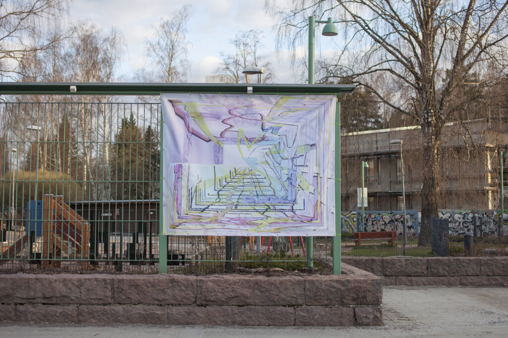 A colourful banner artwork attached to a green fence.