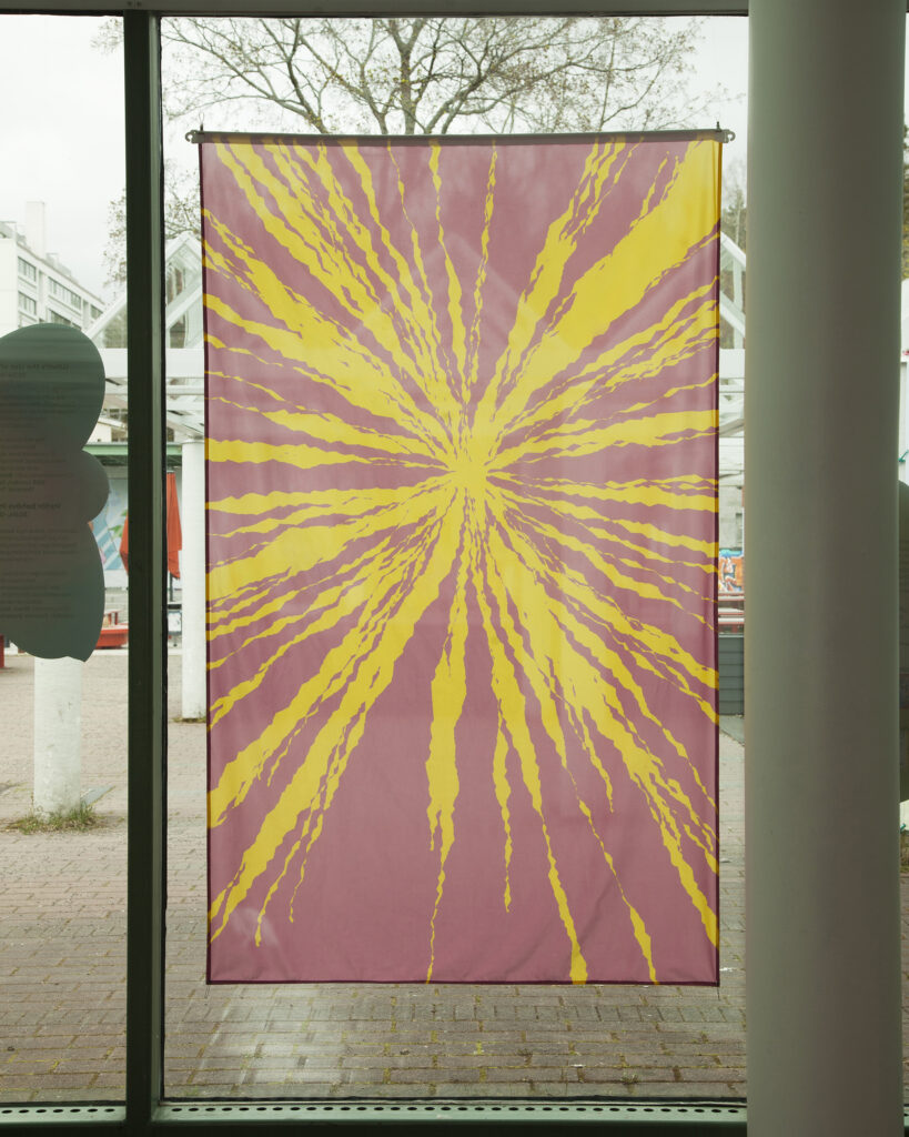 A pink and yellow flag in a window